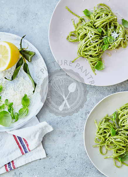 Summer pesto pasta on grey stone background