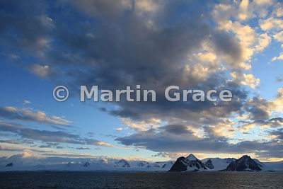 Land in Marguerite Bay, West Graham Land, Antarctica, with evening light on clouds against blue sky