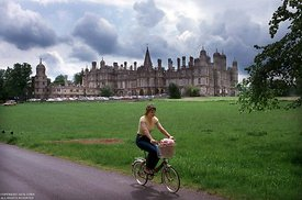 England, Girl on bicycle at Burghley Castle