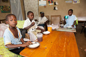 Family enjoying a meal of boiled rice around table  in their home, Kenya.