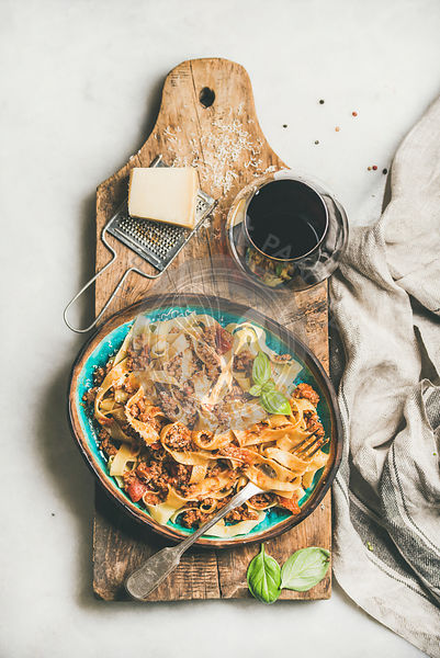 Tagliatelle bolognese with minced meat and glass of red wine