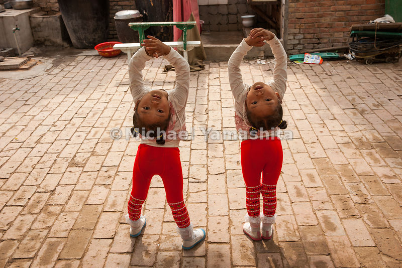 Three-year-old twins are among the youngest students at the Changfa Acrobatic School in Wuqiao County. Their program includes tumbling, juggling and a basic education; tuition, room, and board is $150 a year. Thought the canal is now dry in this area, it once ferried acrobats to performances in port towns.