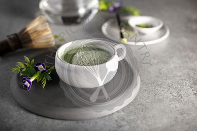 A warm cup of matcha green tea that has just been prepared with wooden whisk and teapot in the background.