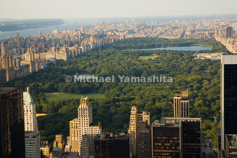 The view from Central Park South extends from the Sheep Meadow, past the Jacqueline Onassis Reservoir, and beyond the park's northern border at 110th Street.  Manhattan, New York City.