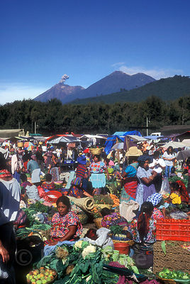 Colors at the traditional Mayan section of the Saturday market in Antigua, Guatemala, with an erupting volcano in the background