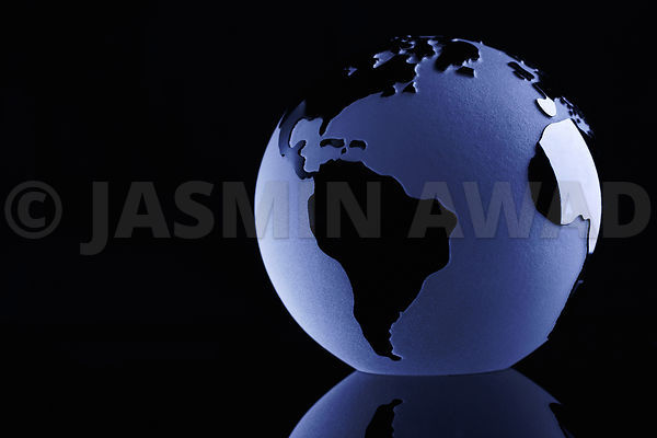 Glass Globe on Black background with reflection and copy space