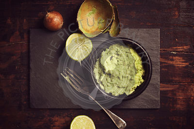 Homemade guacomole sauce on rustic background