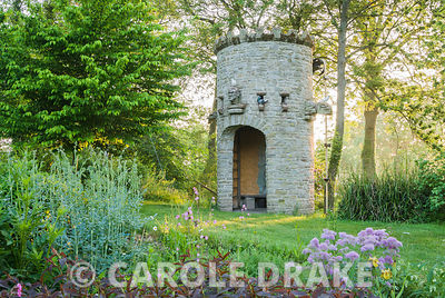Stone dovecot that operates as a spectacular water feature as well. A simple belt and trough system scoops water up from the mill leat into a tank which, when full spouts throught the open mouth of a gargoyle back into the mill pond. Westonbury Mill Water Garden, Pembridge, Herefordshire, UK