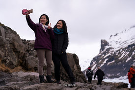 Tourists taking selfies at the Svínafellsjökull glacier in Iceland.