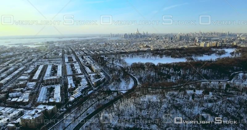 Aerial Over Prospect Park and Pond Snow Brooklyn Brownstones Manhattan in Background NYC