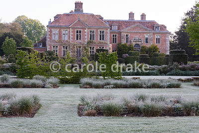 Tussocks of new grass in beds framed by frosty grass at Heale House, Middle Woodford, Wiltshire on a cold April morning