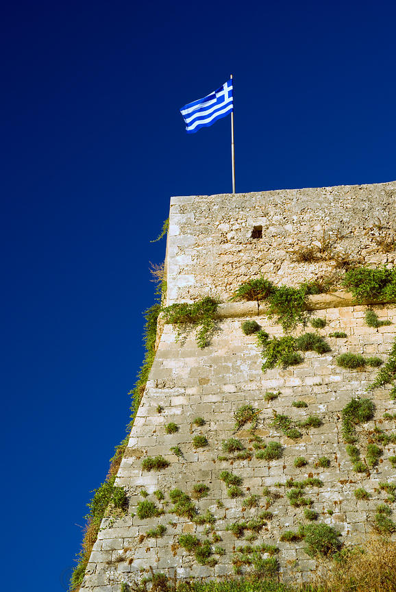greek flag flying from venetian forteza, rethymnon, crete, greece.