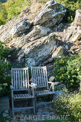 Wooden chairs set against rock outcrop surrounded by rosemary, sedums and wall daisy, Erigeron karvinskianus. The Shute, nr Ventnor, Isle of Wight, UK