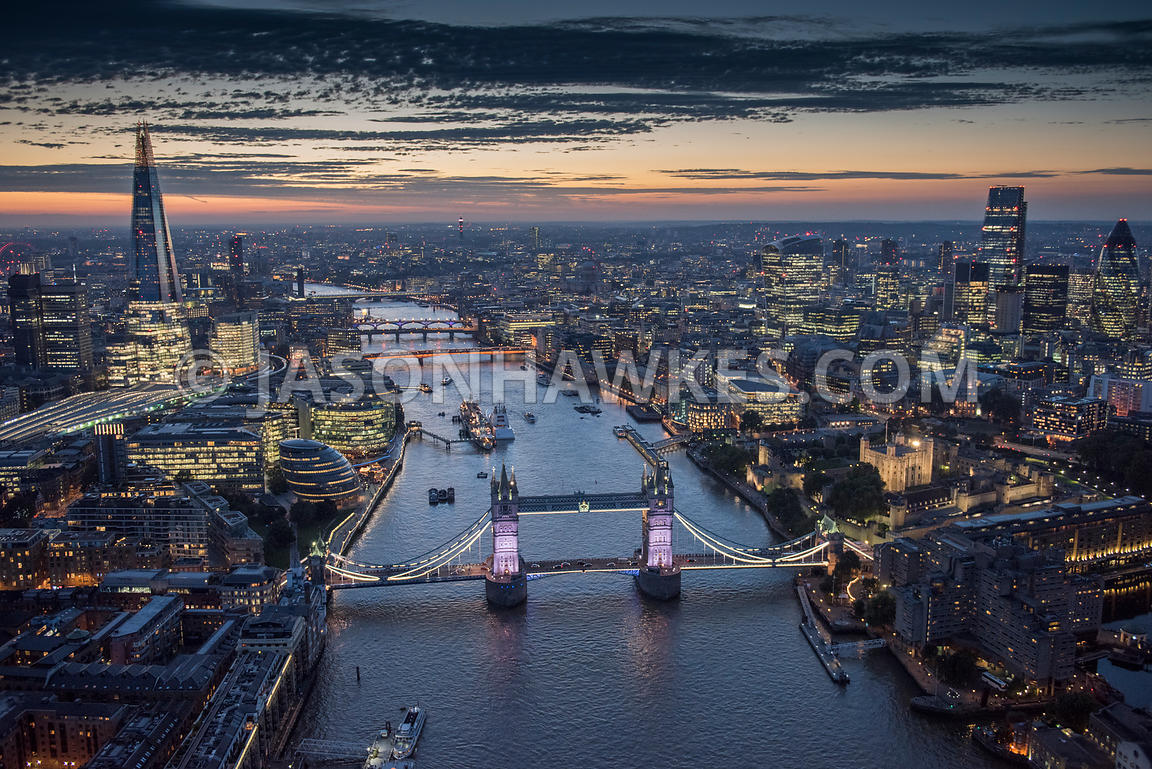Aerial view looking over Tower Bridge at London lit up at night