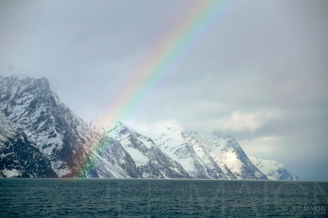 Rainbow over snow-capped mountains and fjord