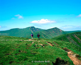 two walkers on the footpath craig cwmoergwm, with the peaks of (l to r) corn du, pen y fan cribyn and fan y big, brecon beacons national park, powys, wales.