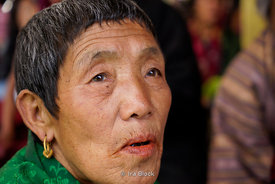 A local woman at a blessing by the Chief Abbot of the Central Monastic Body of Bhutan in Paro, Bhutan.