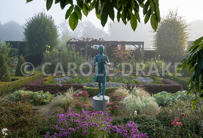 The Formal Garden, with knot garden made of box and berberis, contains a statue of a girl holding the lamp of wisdom by Nathan David. It is surrounded by tall yew hedges and featues a vine covered pergola.  Waterperry Gardens, Wheatley, Oxfordshire, UK