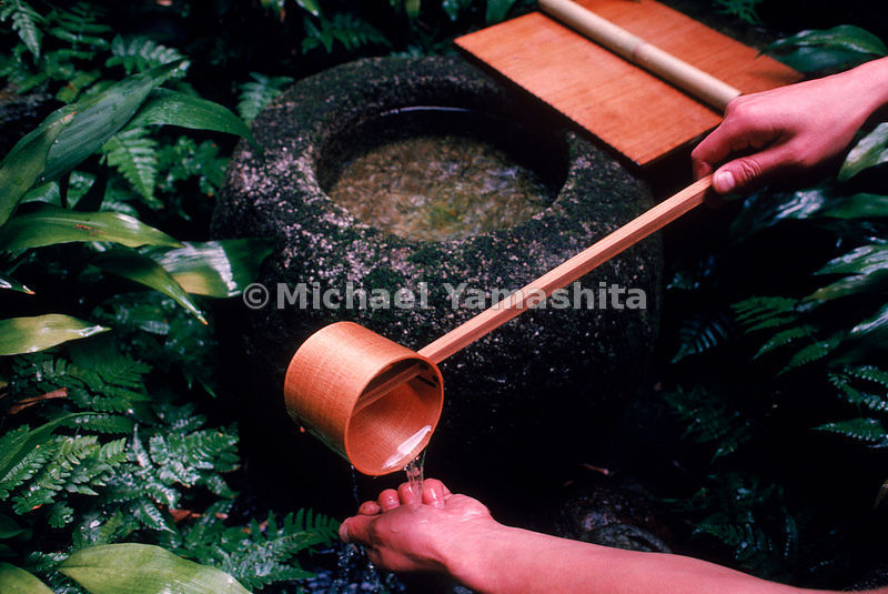 A tea devotee cleanses his hands prior to a ceremony held at the Yabunouchi Tea School in Kyoto, Japan.