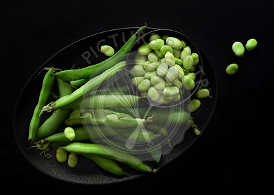 Fava beans in pods and shelled in a bowl.