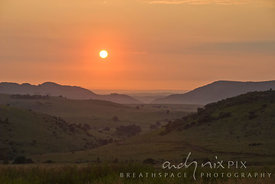 Deep orange sunset over a series of highveld hills.