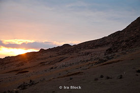 A sunset peaks over the rocky terrain in the Galapagos Islands.