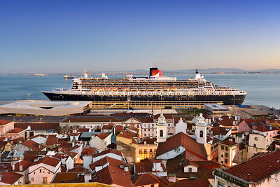 The iconic cruise ship Queen Mary II on the Tagus river facing the traditional moorish Alfama district. Lisbon, Portugal