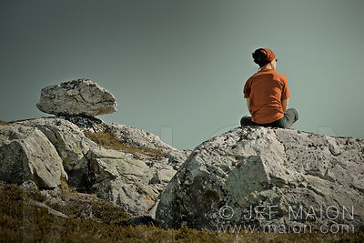 Woman sitting cross-legged on rock