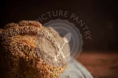 A close, detail shot of a loaf of sesame bread on a rich wood surface.