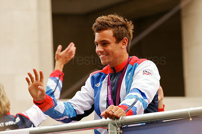 Medal winning diver Tom Daley waves to the crowd from a float during the Olympic athletes victory parade in London.