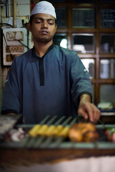 India - Delhi - A cook prepares fresh kebabs at Karim's Restaurant,