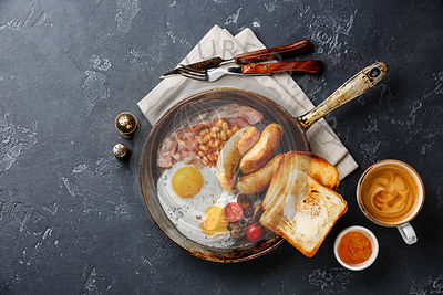 English breakfast in cooking pan with fried egg, sausage, bacon, beans, toast and coffee on dark background copy space