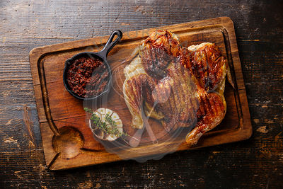 Grilled fried roast Chicken Tabaka on cutting board on wooden background