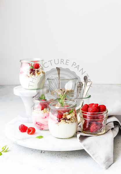 Breakfast Jar filled with greek yogurt, granola, raspberries and  mint leaves