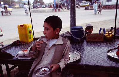 A child eats an onion while working at a tea stall, in Mazar-i-Sharif, Afghanistan