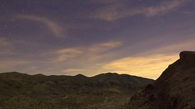 Medium Shot: A Sheer Curtain of Wispy Clouds Frames a Star Filled Sky Over Red Rock Canyons (Day To Night)