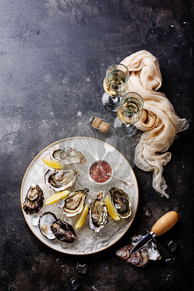 Open Oysters with spicy sauce and champagne on dark stone texture background copy space