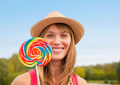 Woman eating lollipop outdoors