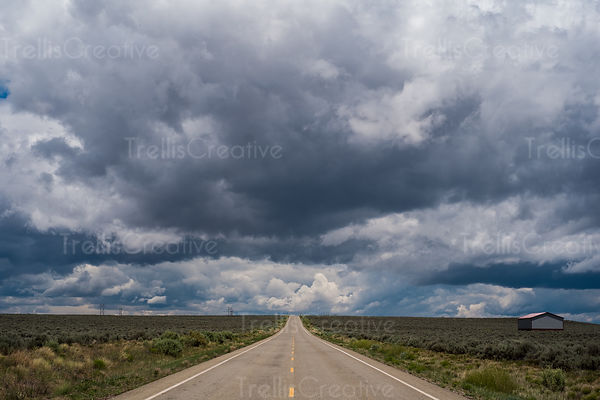 Straight wide open road through green landscape with dramatic cloudscape above