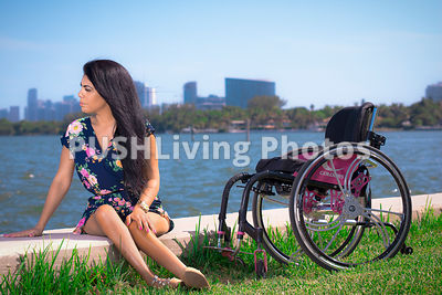 Young woman in a wheelchair in a coastal park