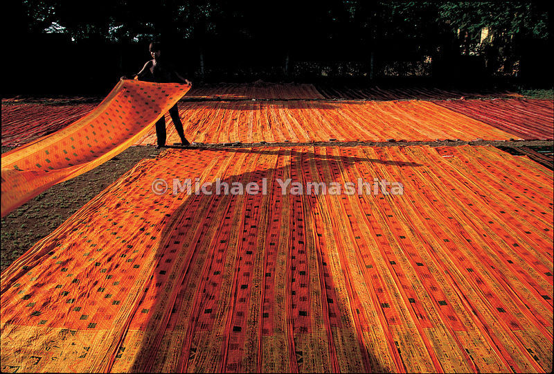 Lenghts of colorful cottons woven in Gujarat create a saffron carpet as they dry.