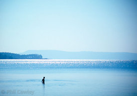 beautiful blue sea with silhouette of girl bathing in the distance