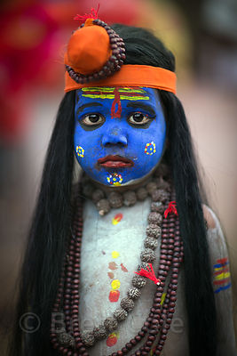 A boy dressed as Shiva poses for photos with tourists during the Pushkar Camel Fair, Pushkar, Rajasthan, India