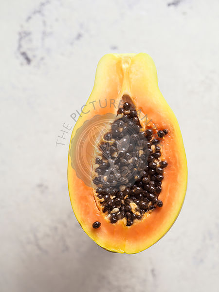 Single papaya cut in half to show flesh and seeds on bright, white, textured background.