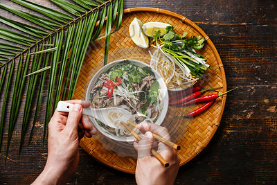 Pho Bo vietnamese Soup with beef and chopsticks in male hands