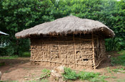 Traditional Kenyan home made from md, with a thatched hut. Kenya.