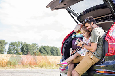 Father and daughter sitting in open car boot looking at camera at break of a road trip