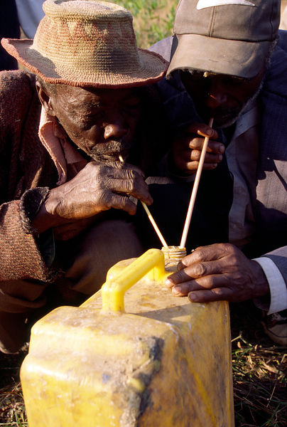 Burundi - Ruyigi - two men settle their differences by symbolically drinking palm wine from the same container.