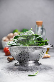 Spinach. Fresh organic spinach leaves in metal colander and healthy ingredients. Diet, dieting concept. Vegan food, healthy eating.