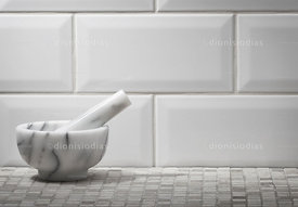 Marble Pestle on bottom of inserts in white tile background